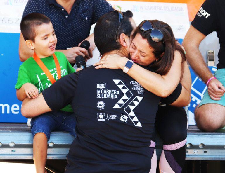 La gerente de APPI, Romina Moya, abraza al padre de Álex, el pequeño de 4 años afectado con el síndrome STXBP1, tras la entrega de medallas a los niños de esta asociación.