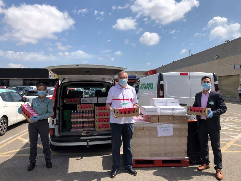 Representantes de Cruz Roja Torrent con trabajadores de Mercadona durante la entrega de hoy